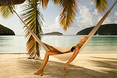 unrecognizable woman in black bikini and summer hat covering her face napping in a hammock at the Caribbean beach