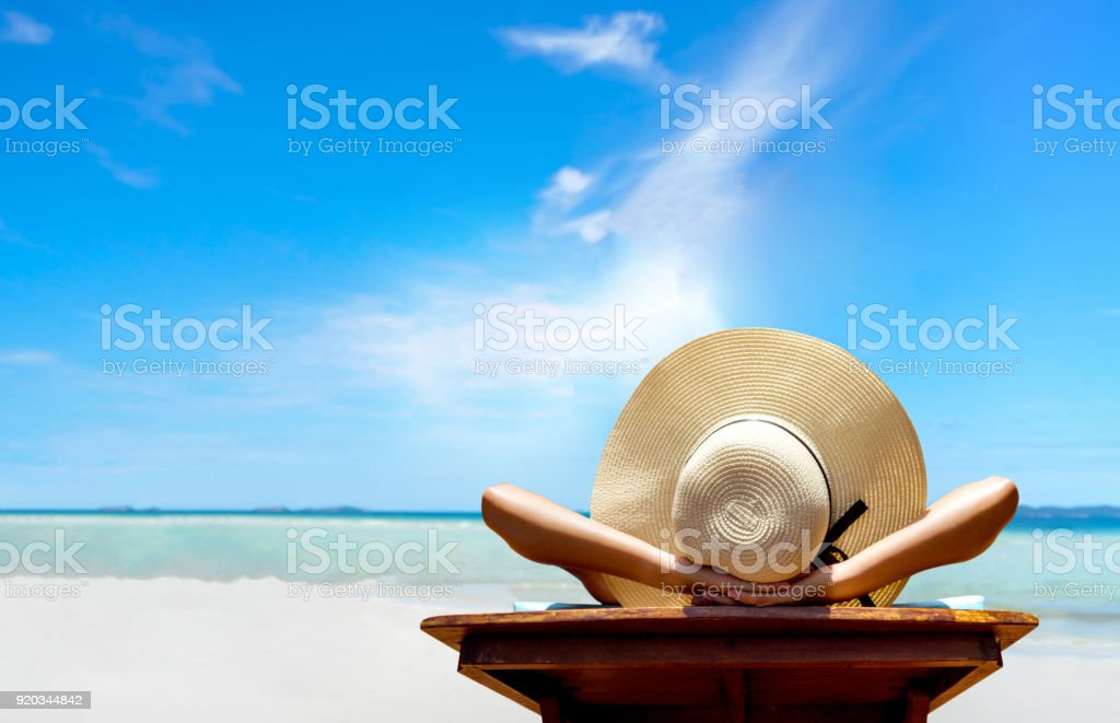 Bikini woman sexy in relax beach and resting resort in vacation on summer season with sunhat sitting chair sunbath with swimsuit alone at island lifestyle on weekend holidays stock photo