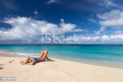 unrecognizable woman in blue bikini and hat lying in sand on a tropical beach in Sandy Point, St.Croix, US Virgin Islands