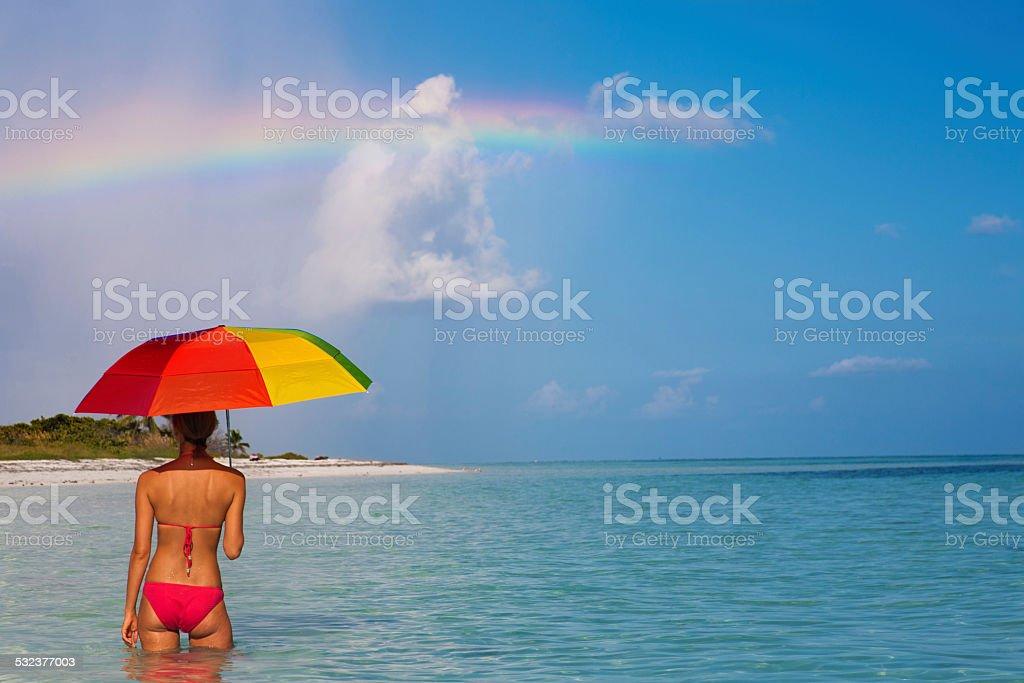 bikini woman with an umbrella watching a rainbow in Florida stock photo
