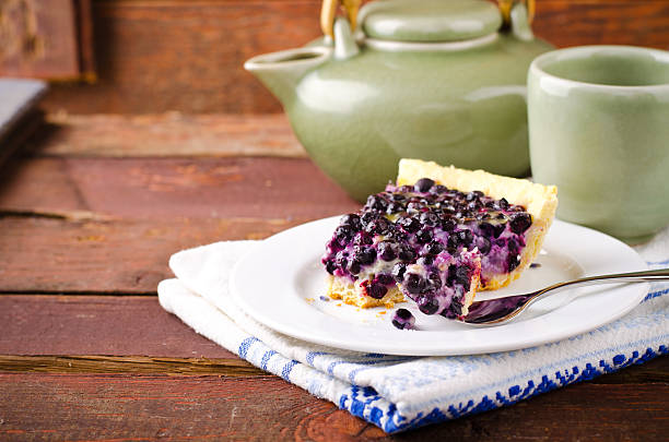 bilberry, blueberry tart with lavender on white plate, wooden background - zitronen heidelbeer käsekuchen stock-fotos und bilder