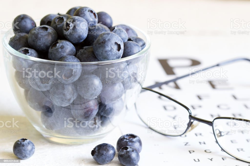 Bilberry cure for eyes concept with glasses royalty-free stock photo