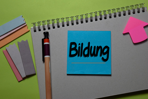 Bildung write on a sticky note isolated on office desk. German Language it means Education