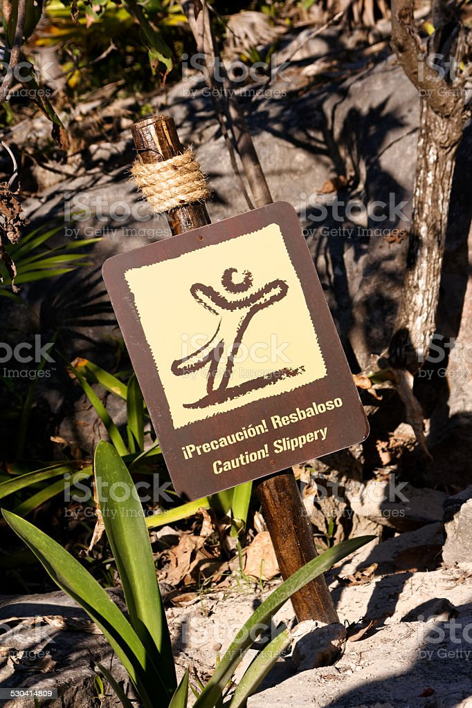 Bilingual Spanish English Sign Caution Slippery stock photo