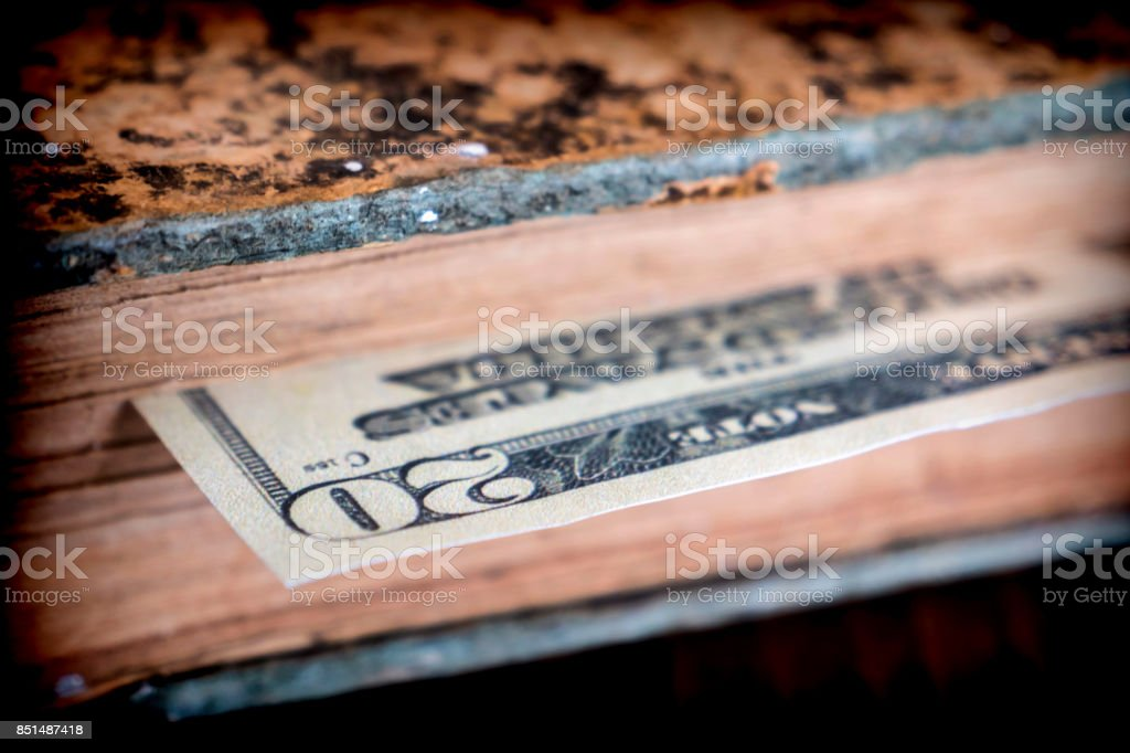 Bill of hundred American dollars hidden in an old book stock photo