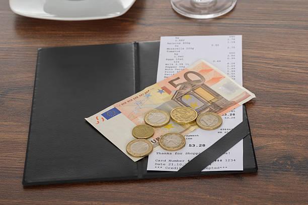bill mit euro-schein auf tisch - eurozahlen stock-fotos und bilder