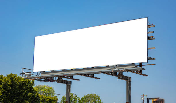 Billboard blank on a highway for advertisement, spring sunny day Billboard blank white color, for advertisement on a highway, spring sunny day, blue sky background, copy space billboard stock pictures, royalty-free photos & images