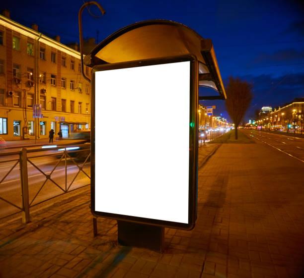 Quadro de avisos sobre a rua brilha à noite. Layout para projeto de publicidade. Lightposter pilão com um campo branco. abrigo de ônibus - foto de acervo