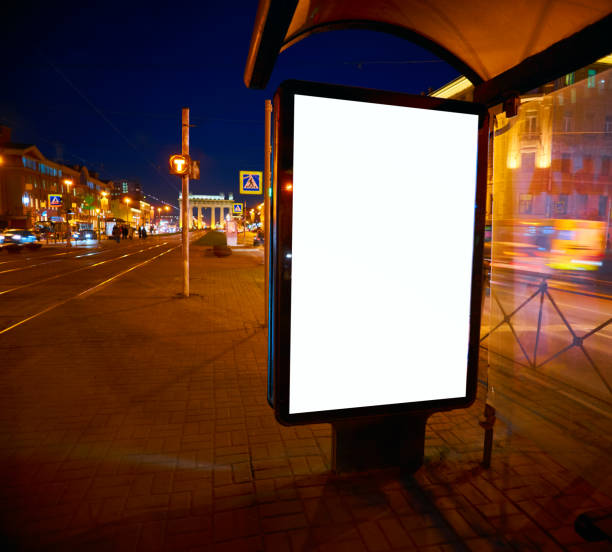 Quadro de avisos sobre a rua brilha à noite. Layout para projeto de publicidade. Pilão de folha com um campo branco no pavilhão de abrigo de ônibus a parar - foto de acervo