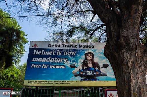Billboard with delhi traffic police warning, depicting a woman with a helmet. Delhi, India.