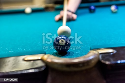 Billiard ball number two near pocket of table