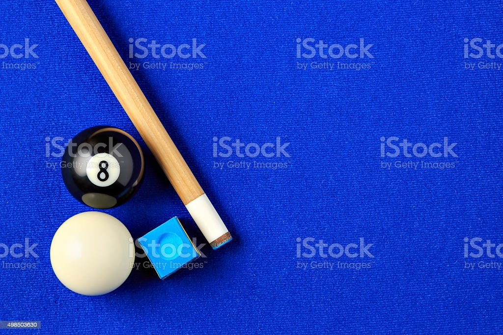 Billiard balls, cue and chalk in a blue pool table. stock photo