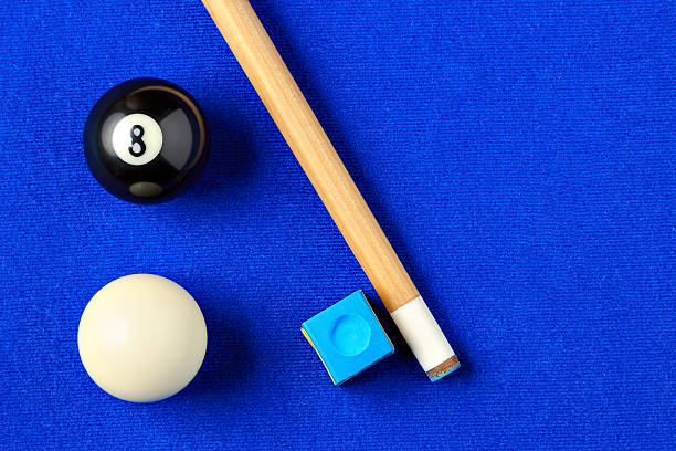 billiard balls, cue and chalk in a blue pool table. - pool cue stock photos and pictures