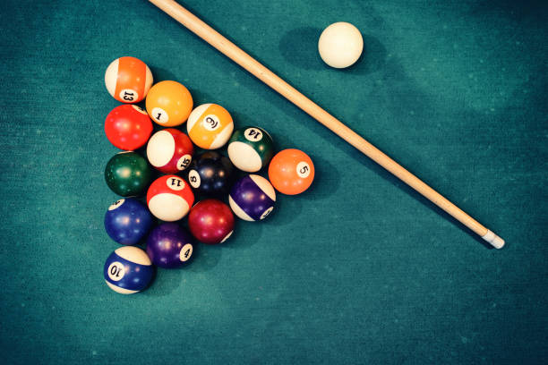 billiard balls in a green pool table - pool cue stock photos and pictures