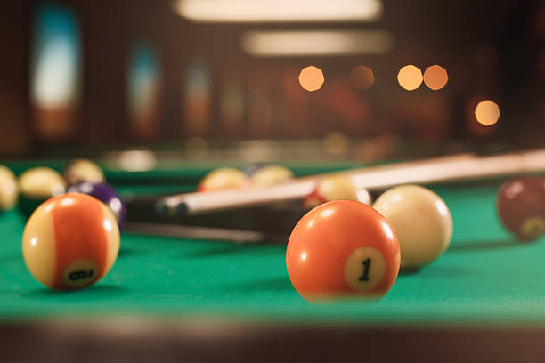 Billiard balls near by cue on the pool table. stock photo