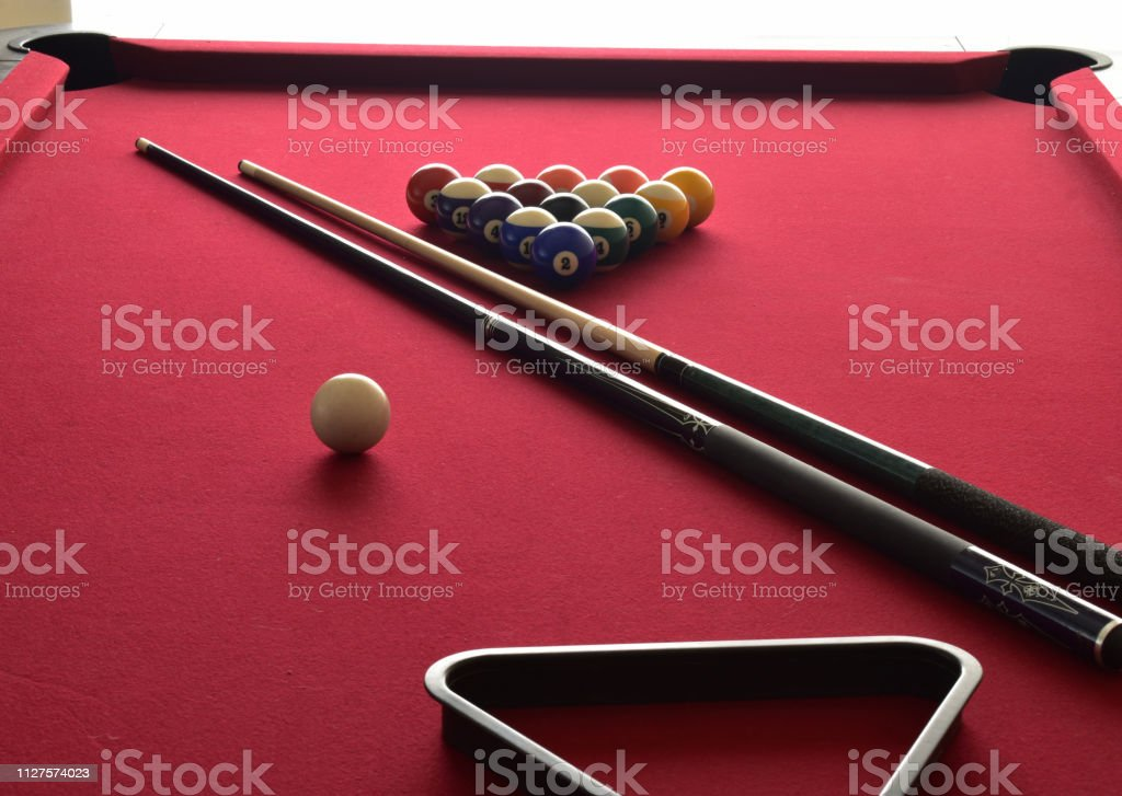 Billiard balls with numbers on them on a red pool table with two...