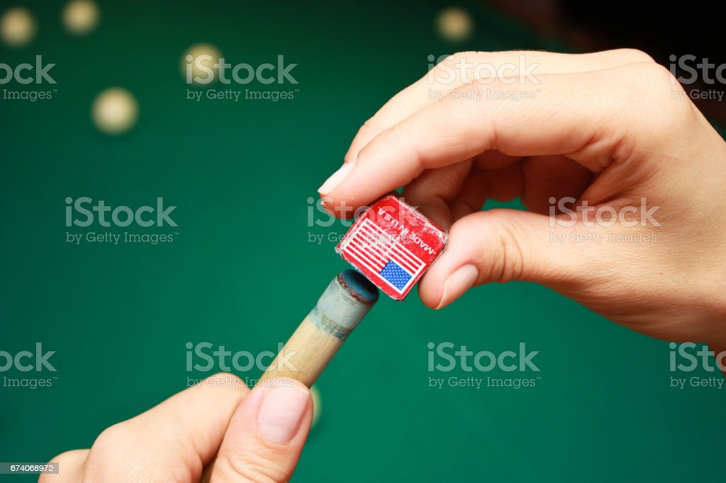 Billiard player rubs chalk his cue. Details of the game of billiards. royalty-free stock photo