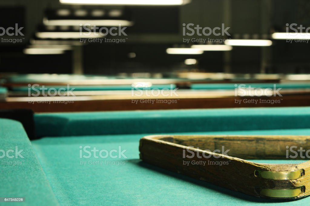 Billiard pool hall with rows of green felt tables and a triangle rack...