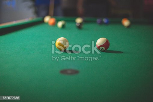 The surface of green billiard  table with two striped balls in foreground and other balls in the background.