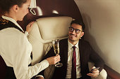 Billionaire travelling in his private jet, holding phone, meeting flight attendant who brings him glass of champagne, enjoying business trip on board