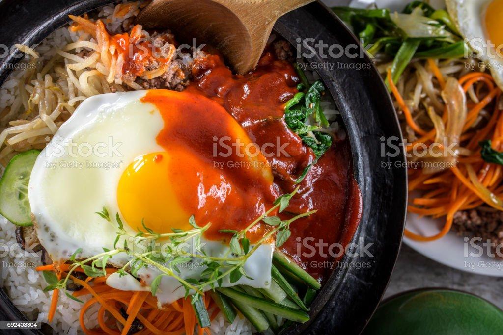 BI Bim Bap, arroz con vegetales mixtos, vista superior con salsa en olla de hierro fundido - foto de stock