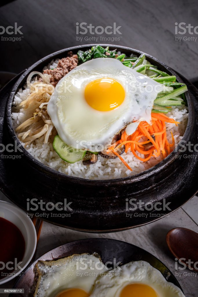 BI Bim Bap, Rice with Mixed Vegetables, top view with Hot Sauce in Cast Iron Pot stock photo