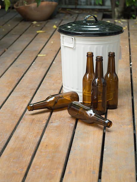 Bin and bottles on rustic wooden floor stock photo