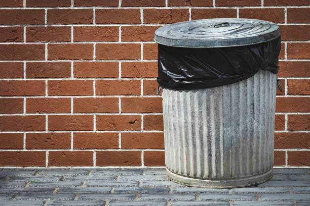 bin and brick wall stock photo