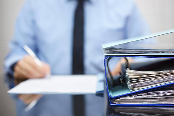 binders  are waiting to be processed  back in blur binders with papers are waiting to be processed with businessman  back in blur. Accounting and business concept bureaucracy stock pictures, royalty-free photos & images