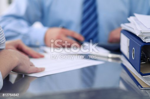istock Binders with papers are waiting to be processed by bookkeepers back in blur. Accounting planning budget, audit, insurance  and business concept 812754542
