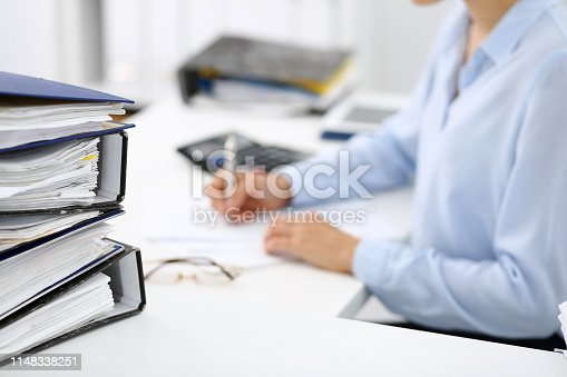 istock Binders with papers are waiting to be processed by business woman or bookkeeper back in blur. Internal Audit and tax concept 1148338251