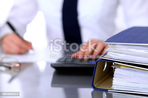 istock Binders with papers are waiting to be processed with business woman back in blur. Accounting planning budget, audit and  insurance concept 685886024