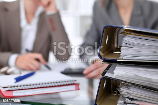 istock Binders with papers are waiting to be processed with businessman and secretary back in blur. Internal Revenue Service inspector checking financial document. 693227568
