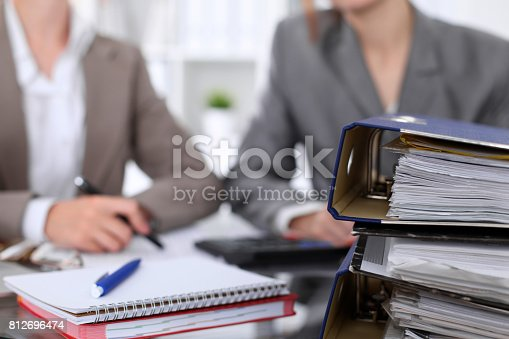 istock Binders with papers are waiting to be processed with businessman and secretary back in blur. Internal Revenue Service inspector checking financial document. 812696474