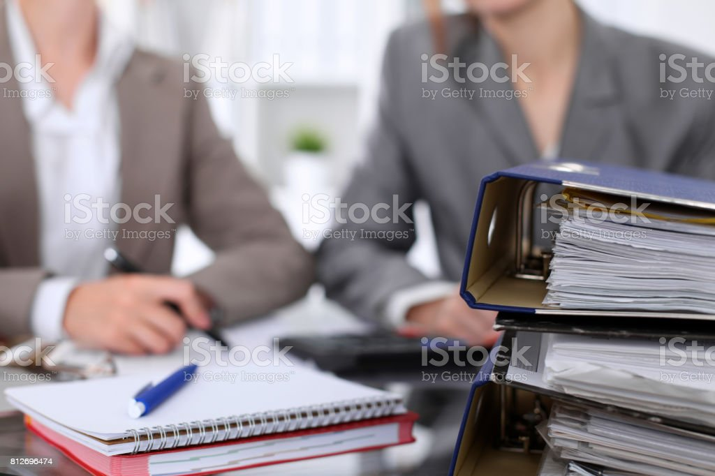 Binders with papers are waiting to be processed with businessman and secretary back in blur. Internal Revenue Service inspector checking financial document. stock photo