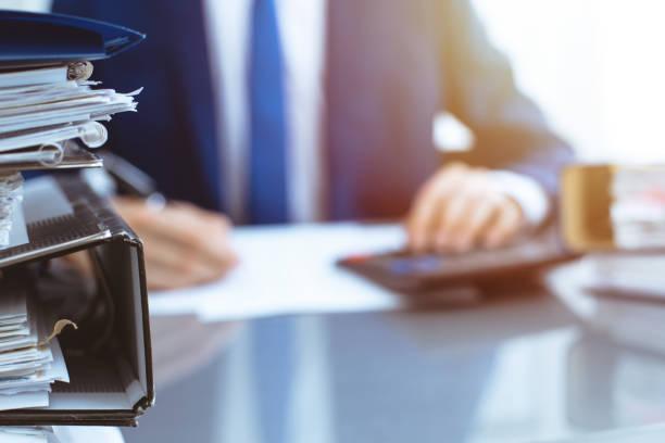 Binder mit Papieren warten darauf, mit Geschäftsmann wieder in Unschärfe verarbeitet zu werden. Buchhaltungsplanungsbudget, Audit, Versicherung und Geschäftskonzept – Foto