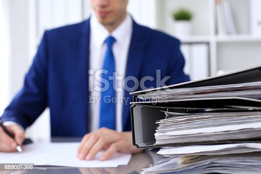 istock Binders with papers are waiting to be processed with businessman back in blur. Accounting planning budget, audit, insurance  and business concept 688001366