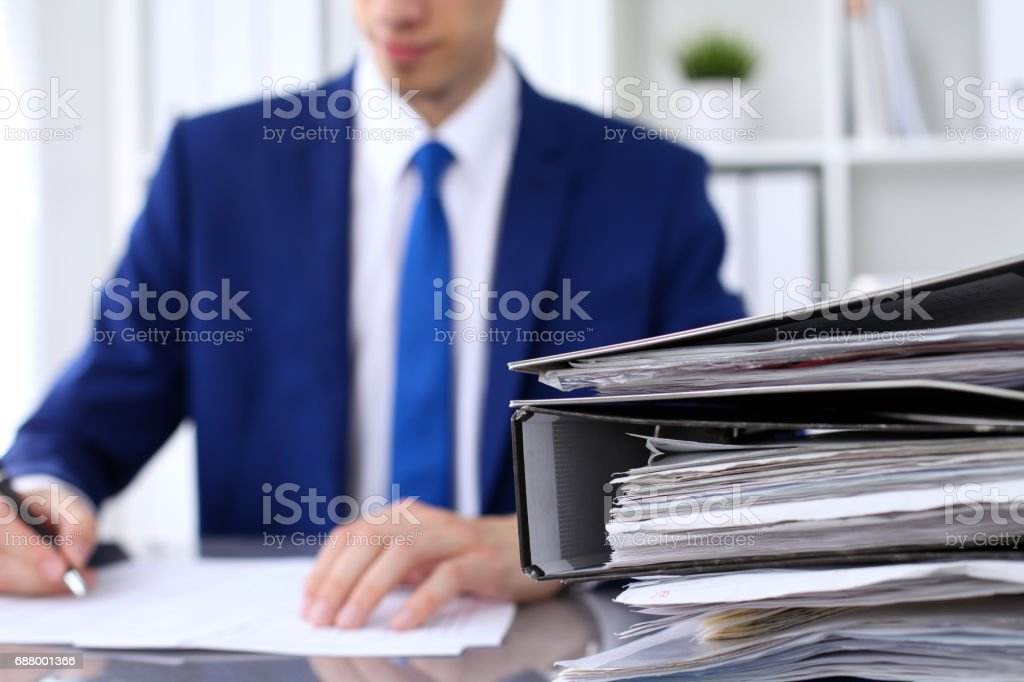 Binders with papers are waiting to be processed with businessman back in blur. Accounting planning budget, audit, insurance  and business concept stock photo