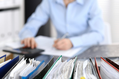 istock Binders with papers are waiting to be processed with businesswoman or secretary back in blur. 1067805214