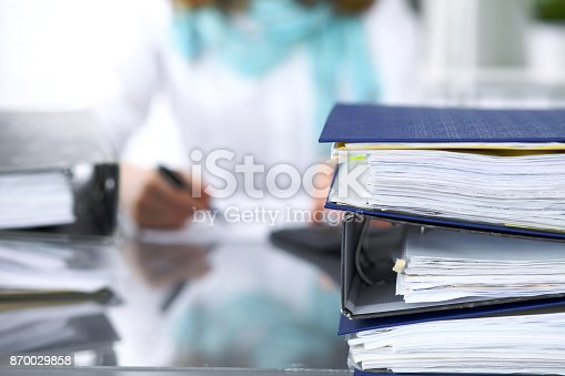 istock Binders with papers are waiting to be processed with businesswoman or secretary back in blur. Internal Revenue Service inspector checking financial document 870029858