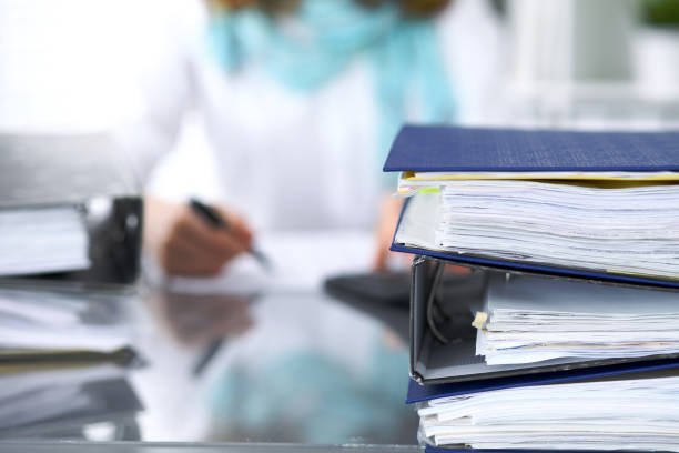 Binders with papers are waiting to be processed with businesswoman or secretary back in blur. Internal Revenue Service inspector checking financial document stock photo