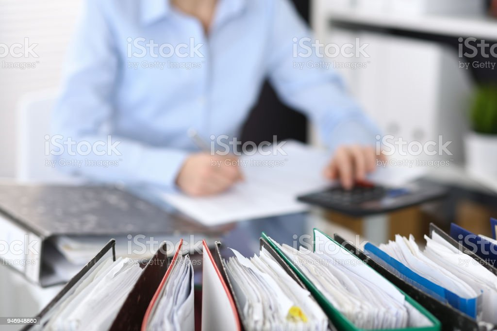 Binders with papers are waiting to be processed with businesswoman or secretary back in blur stock photo