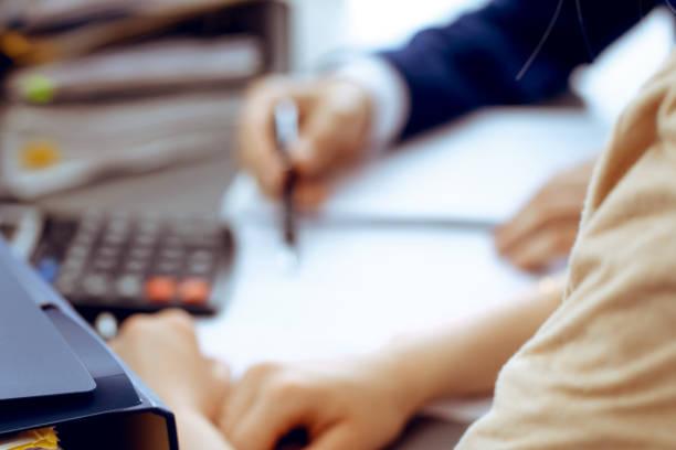 Binder mit Papieren warten darauf, mit Geschäftsmann oder Buchhalter wieder in Unschärfe verarbeitet werden. Buchhaltungsplanungsbudget. Wirtschafts-, Versicherungs- und Geschäftskonzept – Foto