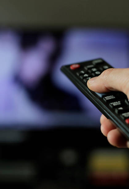 Binge watching TV show A hand with remote control and TV in the background changing channels stock pictures, royalty-free photos & images