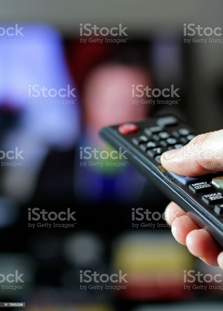 Hand with remote control and TV in the background