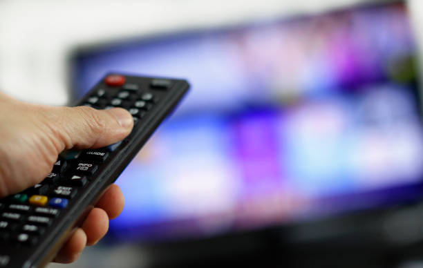 Binge-watching a TV show Hand holding remote control with blurred TV set in the background changing channels stock pictures, royalty-free photos & images
