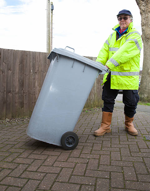 Binman pulling a grey wheeliebin to a nearby trash wagon A Binman taking a grey wheelie / dustbin  to a waiting trash wagon - out of shot. street sweeper stock pictures, royalty-free photos & images