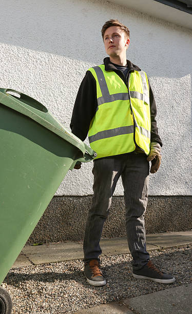 Binman removing refuse - pulling a green refuse bin Young Binman removes a green wheelie bin from a domestic house street sweeper stock pictures, royalty-free photos & images