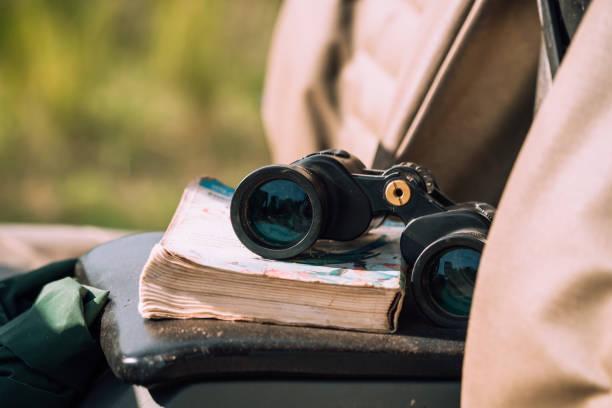 Binocular and book lying in the car stock photo