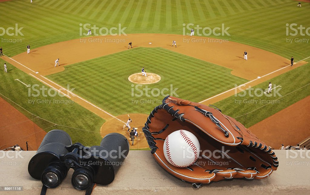 Binoculars and a baseball glove at a ballpark stock photo